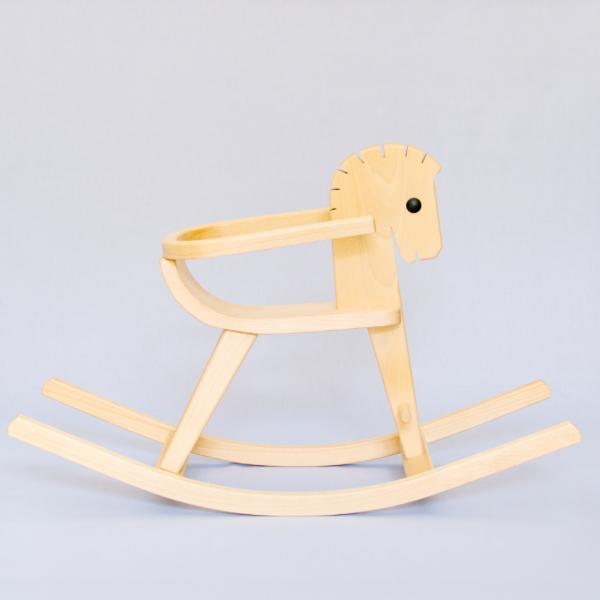 Schaukelpferd aus Vollholz. Die Form des Pferdes ist stilisiert und der Körper ausgeschnitten aus einer Holzplatte ist flach. Dreidimensional wird das Pferd erst durch die addition der Beinstreben und Kufen. Außer dem naturbelassenen Holz hat es nur ein dunkles kreisrundes Auge. Das Pferd hat einen umlaufenden Bügel um den Sitz.
