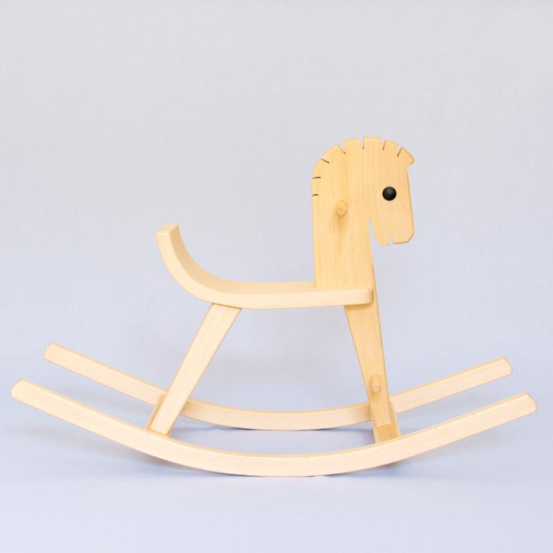 Schaukelpferd aus Vollholz. Die Form des Pferdes ist stilisiert und der Körper ausgeschnitten aus einer Holzplatte ist flach. Dreidimensional wird das Pferd erst durch die addition der Beinstreben und Kufen. Außer dem naturbelassenen Holz hat es nur ein dunkles kreisrundes Auge.